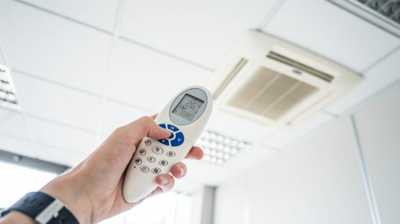 controlling-office-room-temperature-with-air-conditioning-remote-control-picjumbo-com (1)